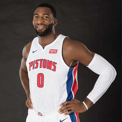Andre Drummond standing in his pistons uniform with the number 0 on the front, smiling with both hands on his hips