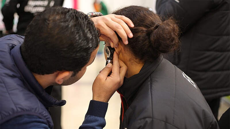 A professional administers an ear exam to an athlete.