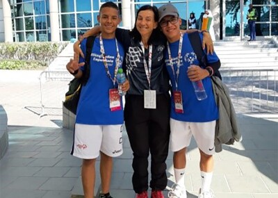 Coach Maria at World Games Abu Dhabi 2019 standing with two athletes on either side of her in front of the pavilion.