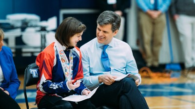Tim Shriver sits next to female student at a high school assembly.