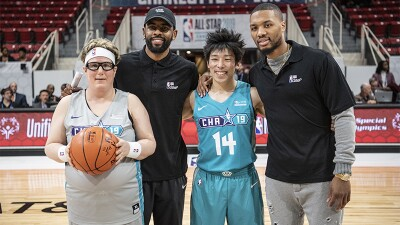 Two NBA players standing behind two Special Olympics athletes on the court.