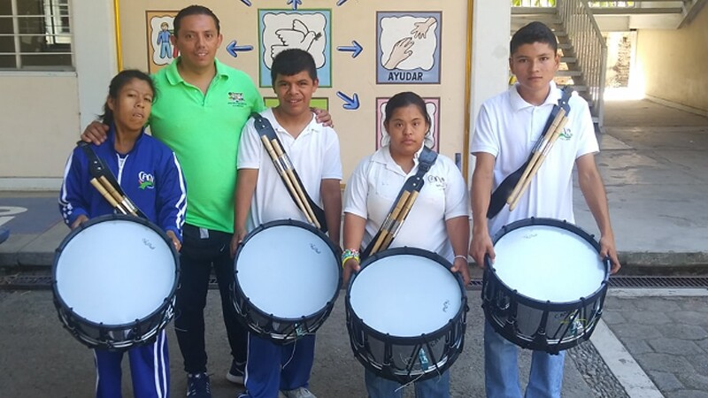Four youth stand outside in a school yard, in school uniforms, holding drums. An adult man stands behind them with his arms around them, smiling.