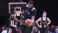 Andre Drummond on the court with two female players, he's handing a basketball to one of the players.