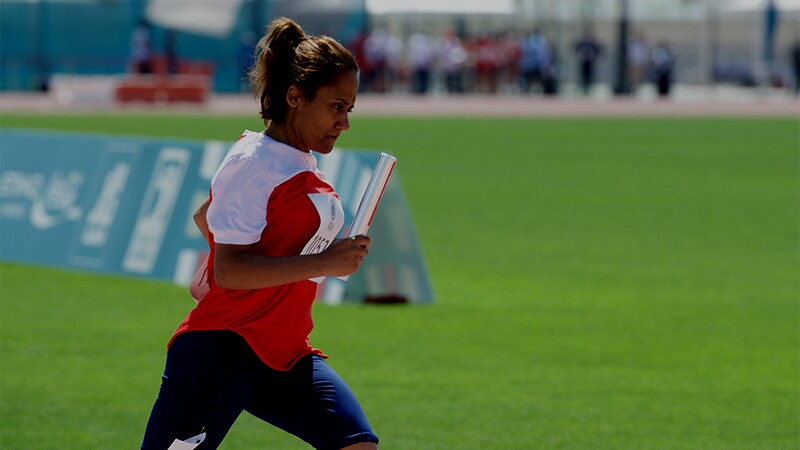 Woman running on a track outside in a group race. She is holding a baton and is wearing a red and white jersey t-shirt and blue shorts; a grassy field is in the background and spectators are in the far background.
