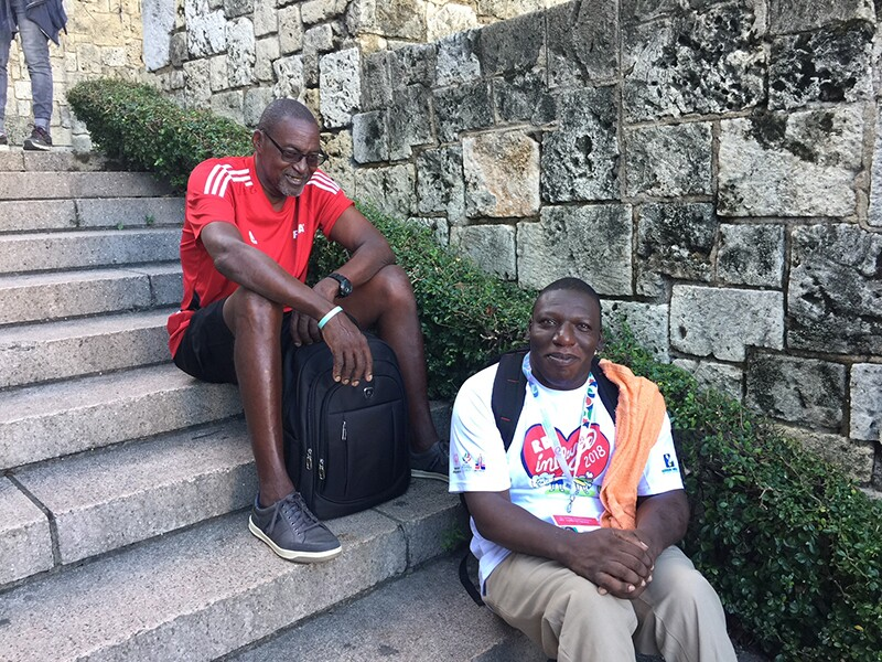 Athlete, Terrence Davis, and another person sitting on concrete steps next to a brick wall.