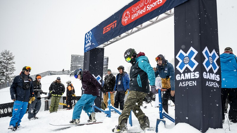 Two people are on snowboards under the starting sign waiting for their race to start. Other people are standing and watching them.