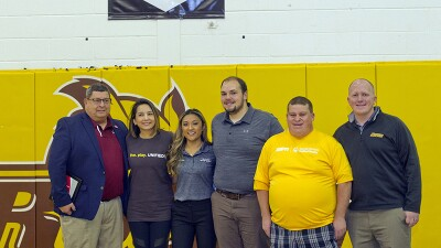 A group of 6 young adults and Rowan and EPSN representatives stand under a Rowan University Unified Champion Schools banner in a gymnasium.