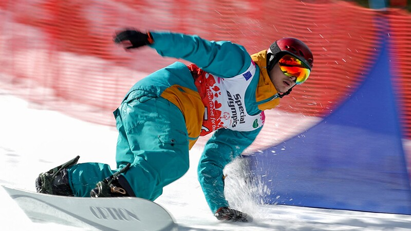 A snowboarder snowboarding down the slopes.