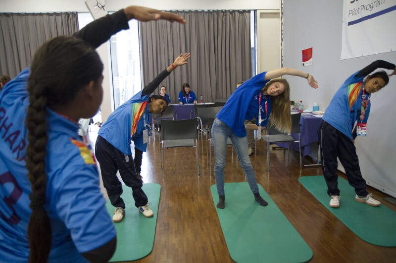 Three Special Olympics athletes at a Strong Minds event stretching on green mats. An instructor is in the front of the room demonstrating fort the athletes and two observers are in the back of the room.
