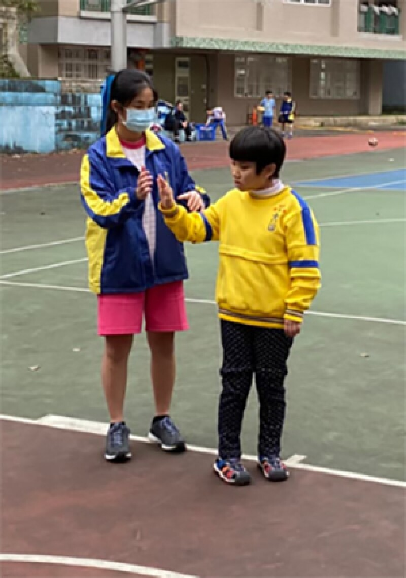 An action shot of two girls high-fiving each other on an outside basketball court.