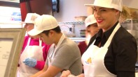 a woman smiling in the pizza kitchen, her coworkers are next to her.