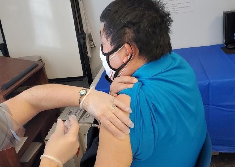 Joe Wu Wilsee receives at COVID-19 vaccination.