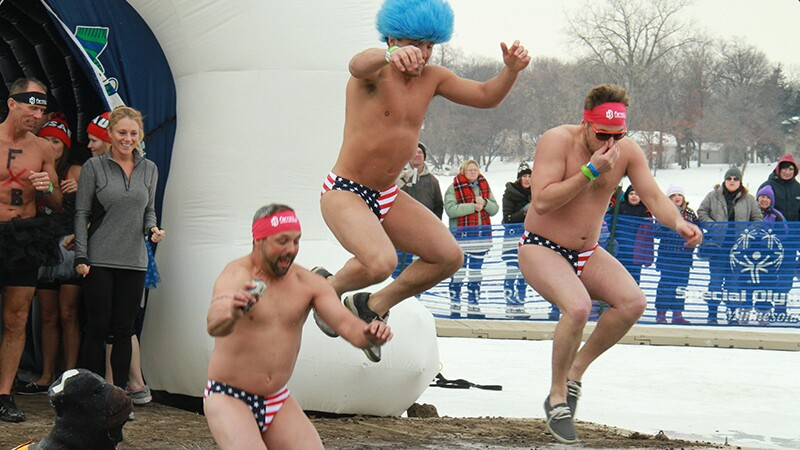 Three guys in USA swimming briefs jumping into that water at the Anoka County Polar Bear Plunge.