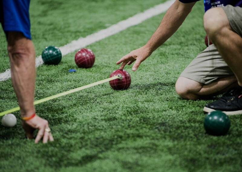 Official on the field measure the distance between two balls as a player observes.