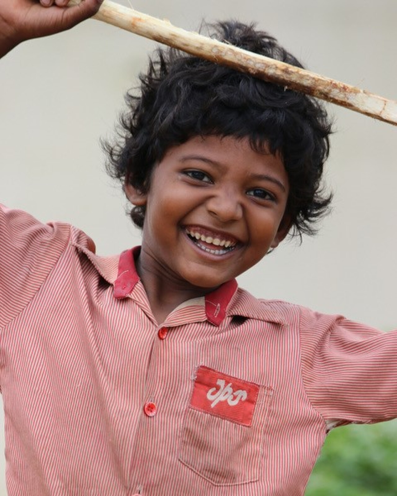 A young child looking at the cameraman and smiling. He is holing a stick above his head and he is wearing a white and red pinstriped button up shirt.