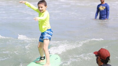 Young boy surfing with two observers watching.