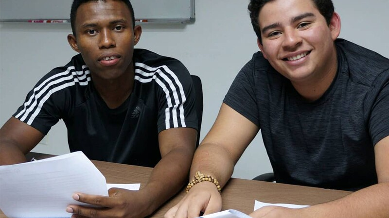 Exsaul and Rodrigo sit at a desk next to each other, each holding papers and smiling at the camera.