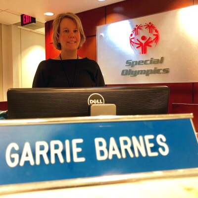 Garrie Barns at Special Olympics standing behind the receptionists desk.
