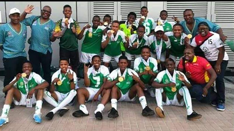Moeti Clement Sethunya with his football team. The players are showing off their first place medals.