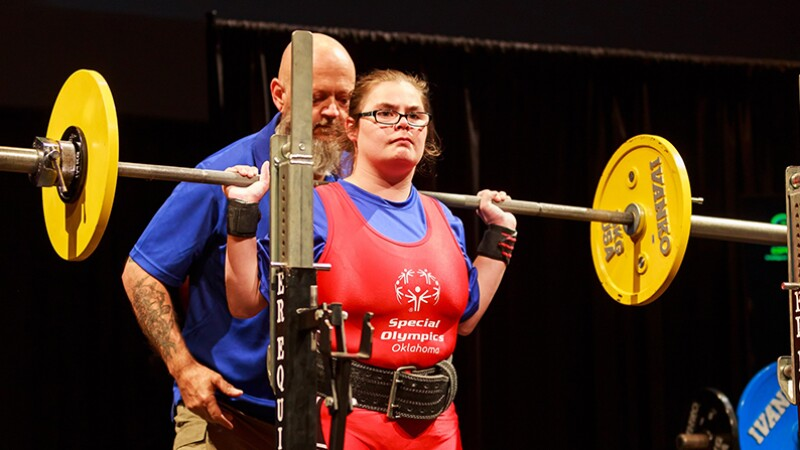 "Weight lifter Elizabeth ""Liz"" Huber, Walmart associate and 2018 Special Olympic USA Games powerlifting athlete on stage with the weight on her shoulders in a fulls stand."
