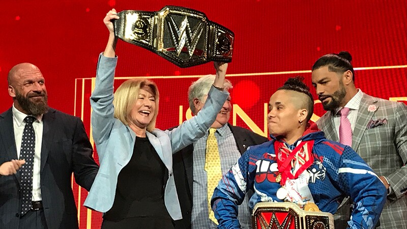 Mary Davis holding up a championship belt on stage with WWE representatives behind her. Special Olympics New York Athlete Angel (power lifter) stands in the center with a champion ship belt around her waist.