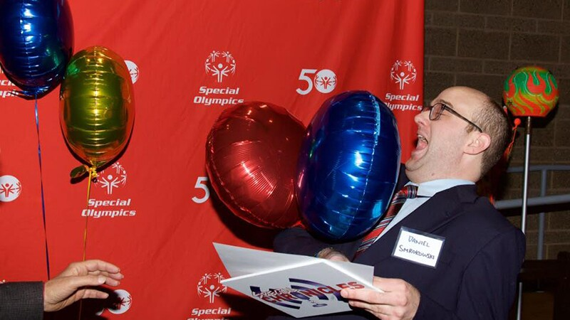 Dan celebrating his 10 years of his podcast, he's holding balloons and is standing in front of a Special Olympics background.