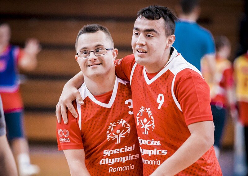 Two athletes from Special Olympics Romania on the court with their arms around one another's shoulders showing camaraderie.
