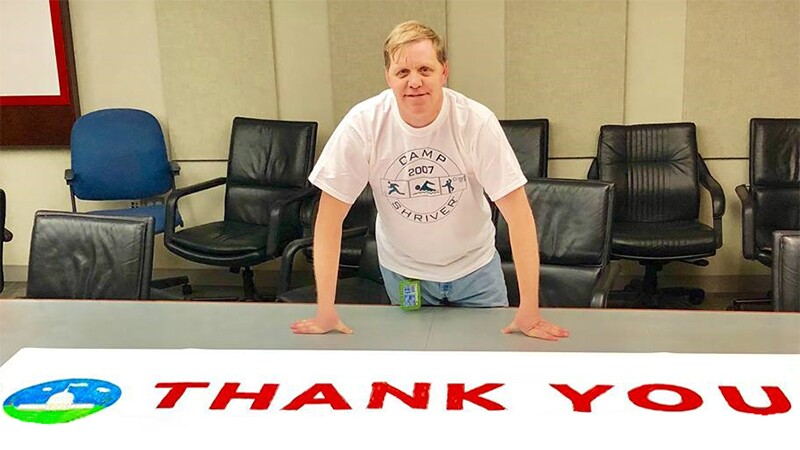 """Robert """"Bobby"""" Jones leaning over with his hands on a conference room table with a sign that reads """"Thank You"""" sprawled across the table in front of him."""