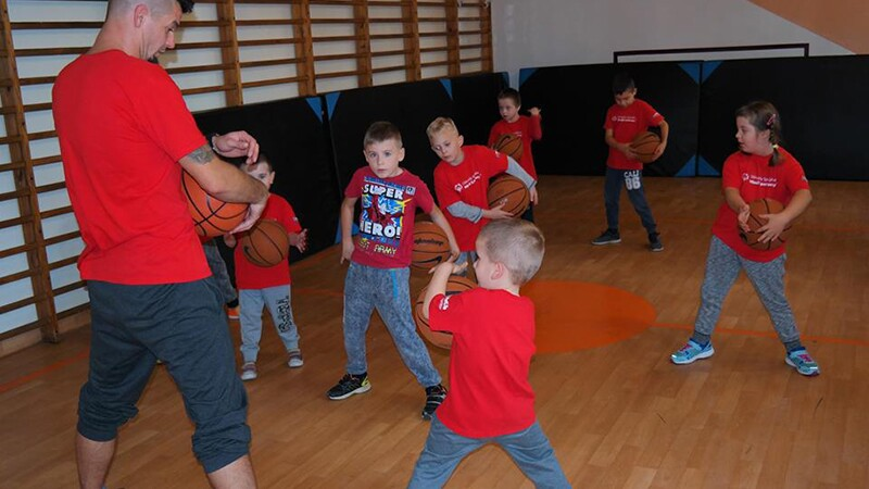 Mini-Basketball activities organised by Special Olympics Poland for European Basketball Week 2017. One professional in a gymnasium of 7 young athletes. All have on red t shirts and are holding basketballs.