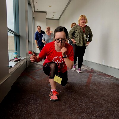 Young girl performing lunges down a hallway while being observed by 4 individuals in the background.