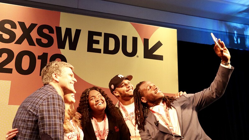 Small group of athletes and Special Olympics representatives pose for group selfie taken by Jamaal Charles in front of the SXSW EDU 2019 sign.