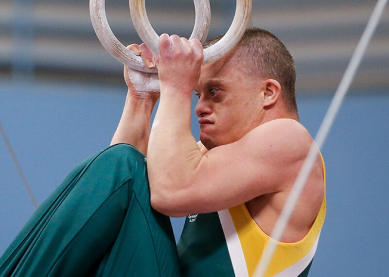 Male athlete tucking on the rings