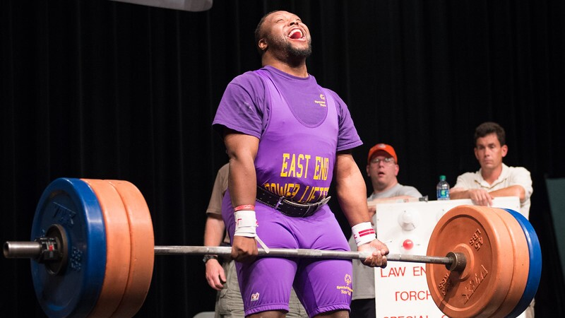 Young adult male athlete performing deadlift as judges and officials watch.