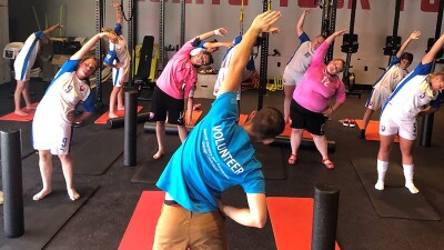 Athletes working out and following the instructions of a volunteer instructor while stretching out in a gym.