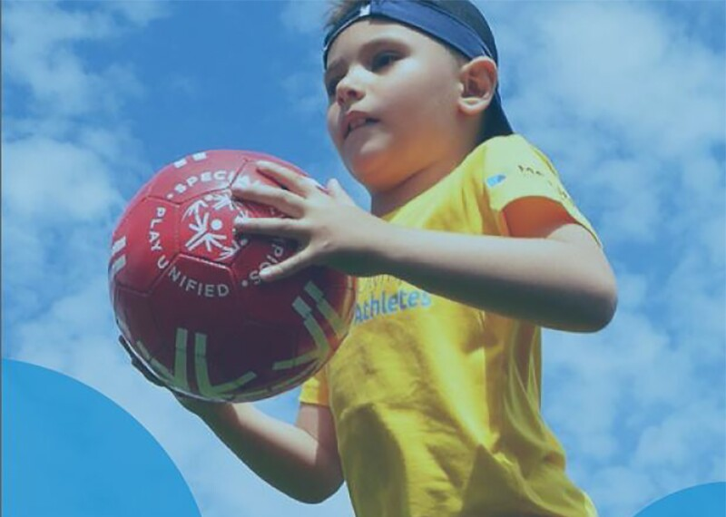A boy in a yellow shirt holding a red Special Olympics Play Unified soccer ball.