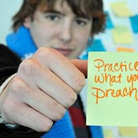 Soeren Palumbo holding up a post-it that reads: Practice what you preach.