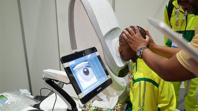 Mohammed Mubarak receives an eye screening at Opening Eyes; his face is being pressed against a machine by a volunteer and his eye is being examined and photographed by a machine.