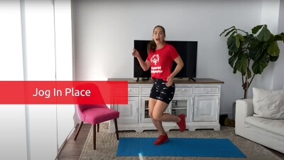 Shannon Decker jogging in place in her living room for a workout video.