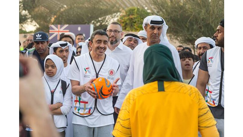 H.H. Sheikh Abdullah kicks off the Walk Unified event in November with other Special Olympics athletes. H.H. Sheikh Abdullah is holding a football and preparing to toss it to an athlete.