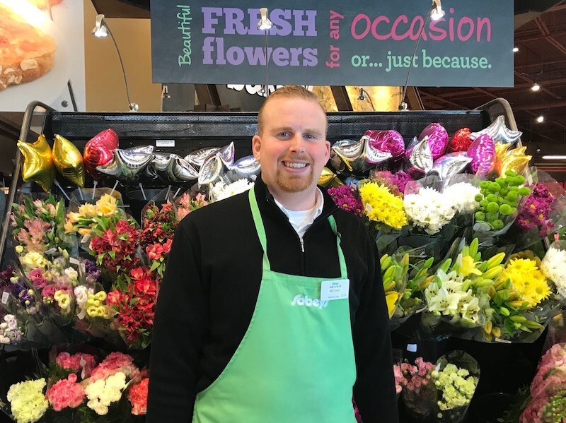 A Special Olympics athlete stands in front of a flower display, smiling at the camera. He's wearing a green apron that says Sobeys.