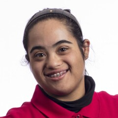 Maryam standing for a professional photo wearing a red long sleeve Special Olympics polo.