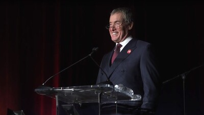 John C. McGinley standing behind a podium smiling and giving a speech at a formal affair.