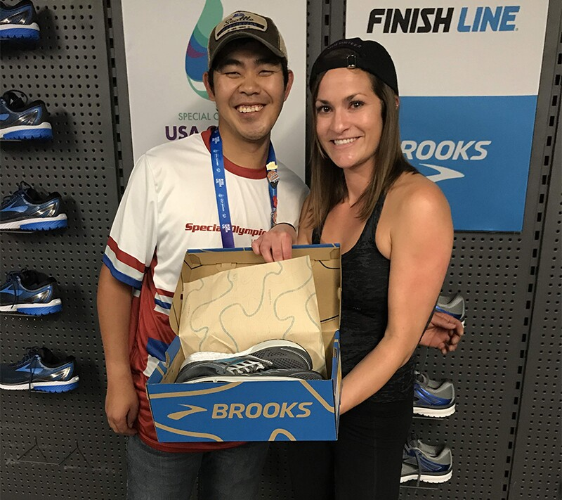 Finish Line Youth Foundation employee presents a Special Olympics athlete with a new pair of shoes