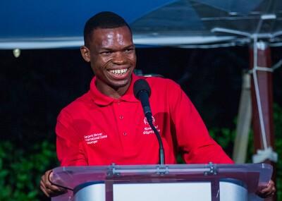 Nyasha standing behind a podium and smiling at the crowd.