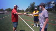 Coach and athletes on the field; coach is squirting hand sanitizer in an athletes hand.