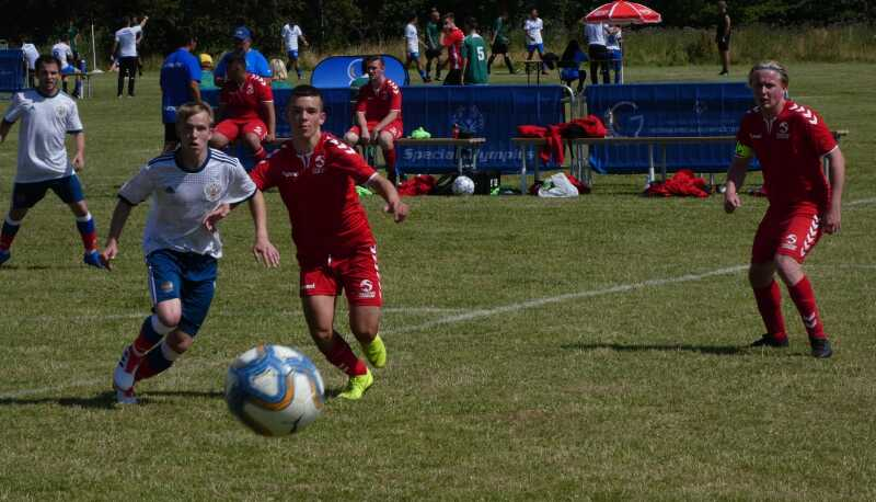 Two men in football kits on a football pitch chase the ball in the foreground of the photo.