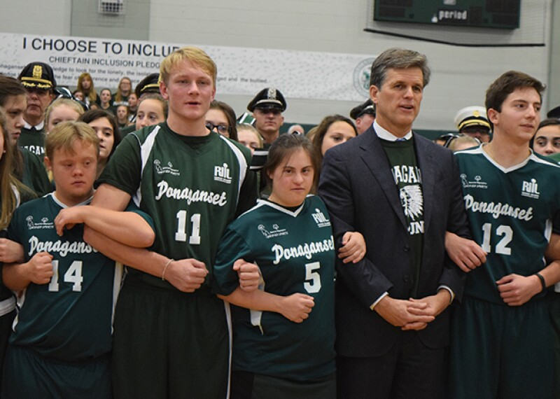 Tim Shriver stands arm in arm with athletes, students, and representatives from a Unified School. Students and athletes are in school colors (green).