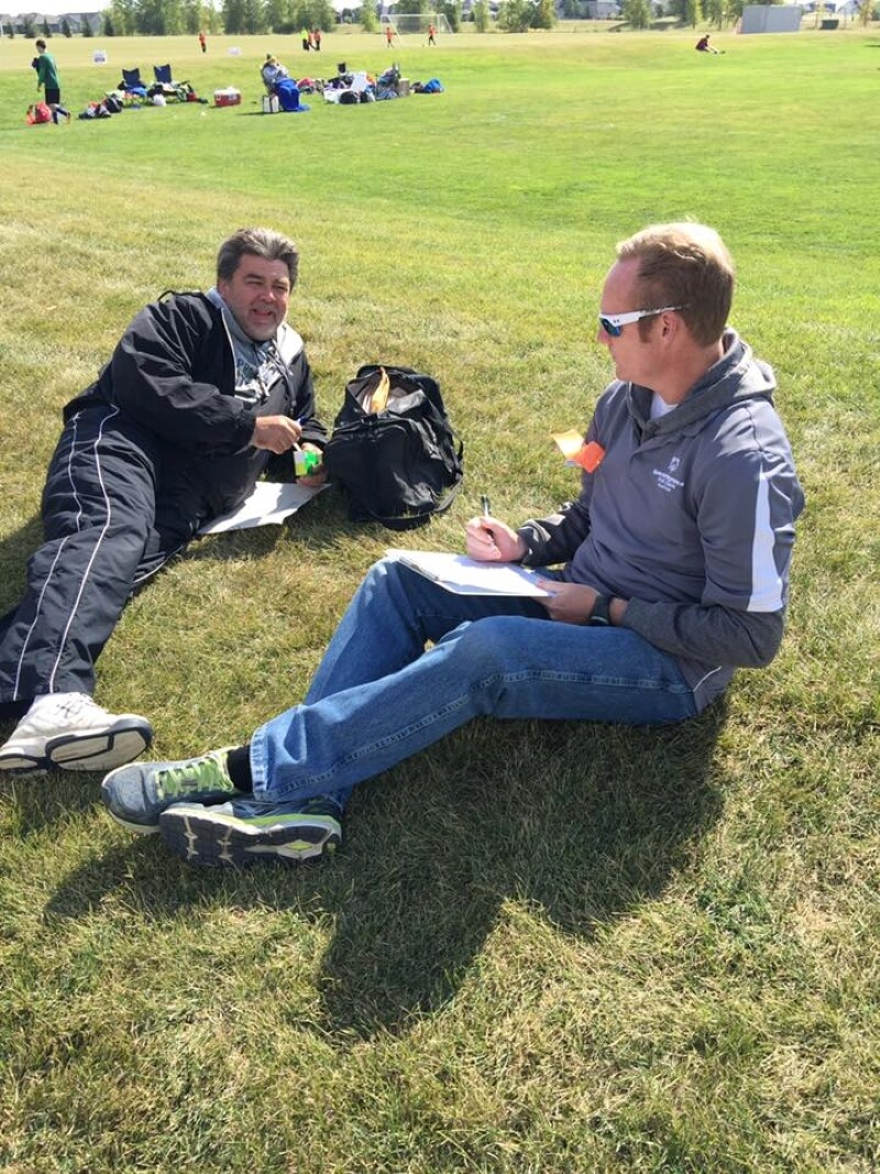 Two Special Olympics North Dakota coaches sit on the grass.