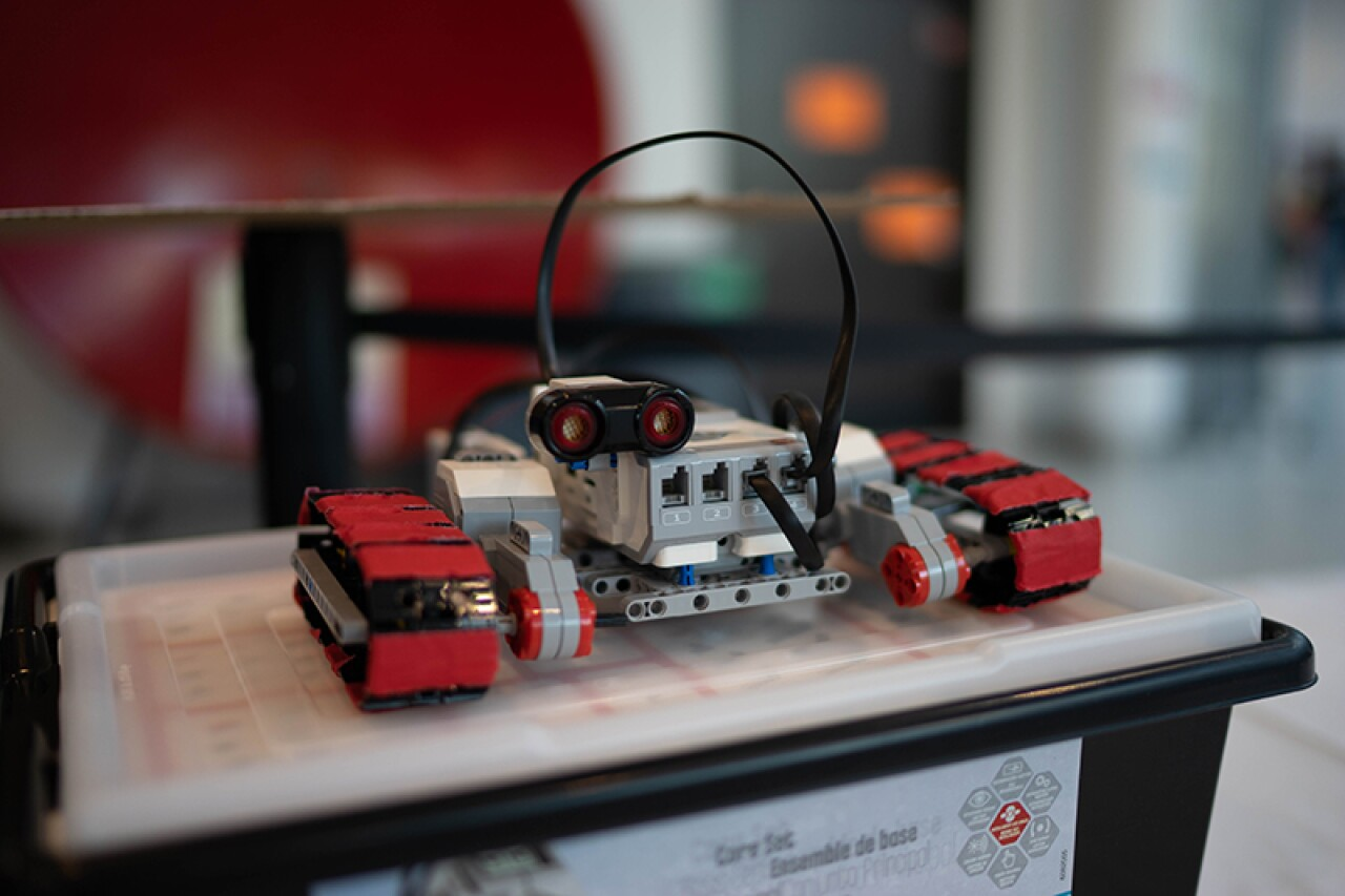 Photo of a robot with two visual sensors, tire treads, and cords coming out of the top.