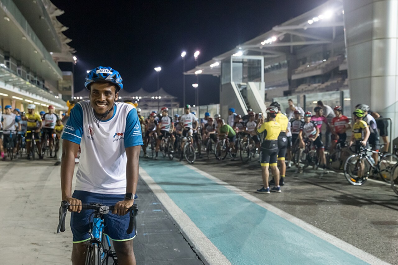 Unified athlete poses on his bicycle ahead of the starting line. Other cyclists are in the background.